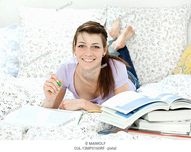 Female student lying in bed, learning