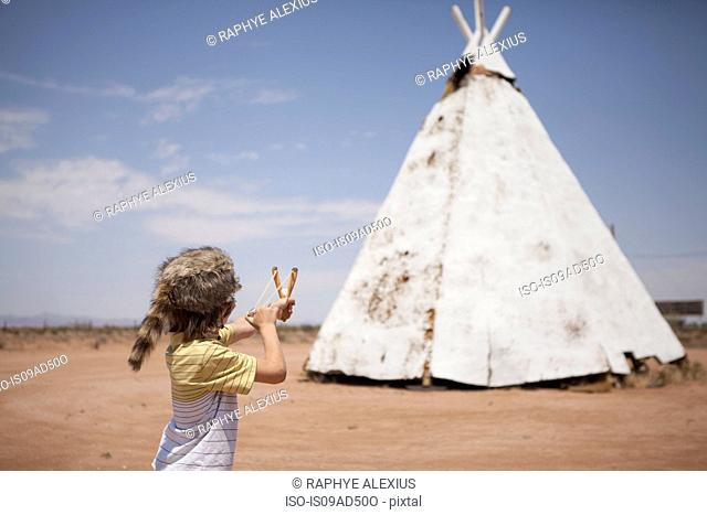 Boy aiming slingshot at teepee, Indian Reservation, USA