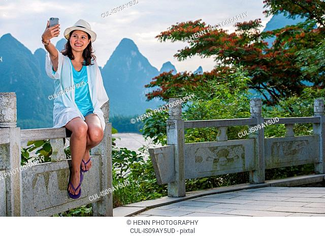 Woman taking a selfie with the karst mountain of Guangxi, China