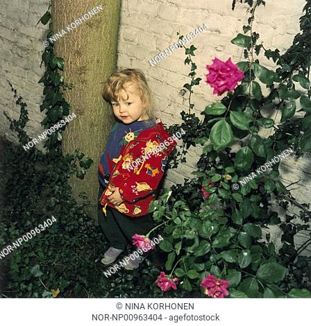 A young girl hiding in the garden with flowers
