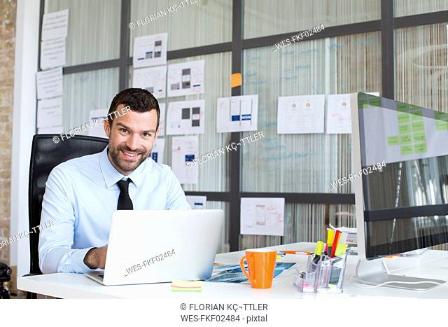 Portrait of smiling businessman in office using laptop at desk