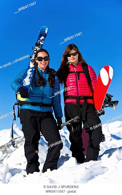 A skier and snowboarder having fun