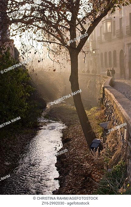 View along the Carrera del Darro river in afternoon sunhaze in December in Granada, Andalucia, Spain