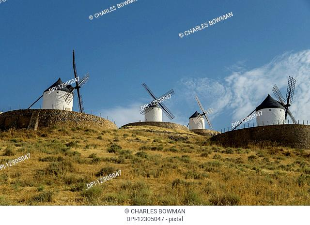 Windmills in a row against a blue sky; Consuegra, Spain