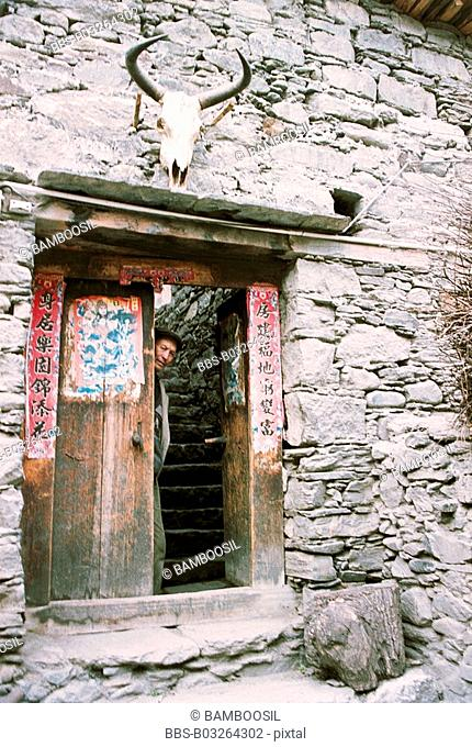 Portrait of a man standing by door of house in Ganbao Zang minority village, Li County, Aba State, Sichuan Province of People's Republic of China