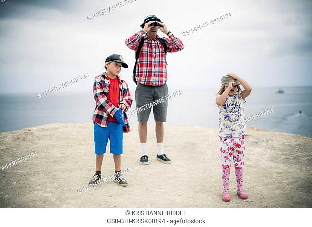 Father Looking Through Binoculars While with Two Children on Coastal Cliff