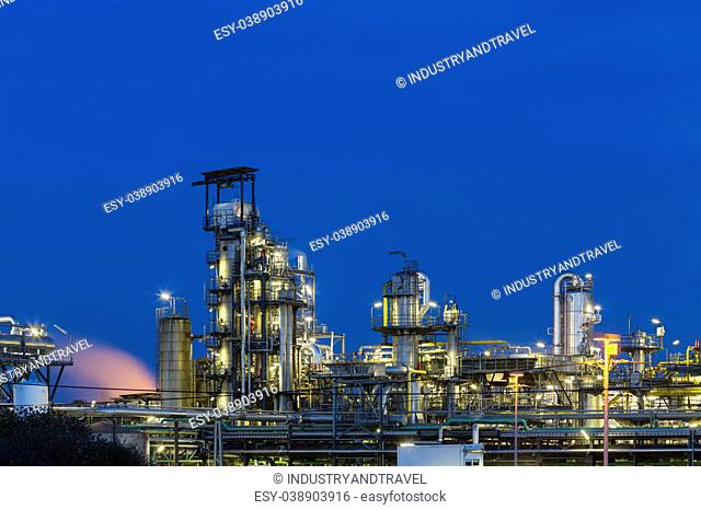 View to the distillation towers of a chemical plant and refinery with night blue sky and illumination