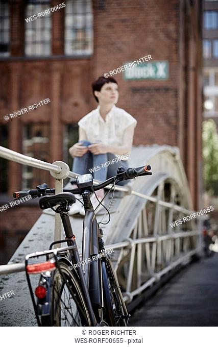Germany, Hamburg, electric bicycle leaning against railing on a bridge
