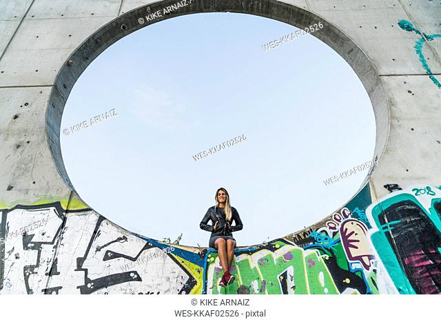 Smiling young woman sitting in a large hole in a concrete wall