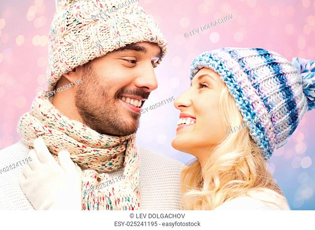 winter, fashion, couple, christmas and people concept - smiling man and woman in hats and scarf hugging over rose quartz and serenity lights background