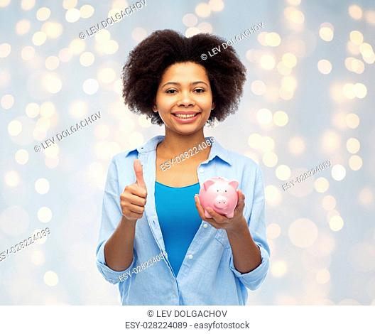 people, money saving and finances concept - happy african american young woman with piggy bank showing thumbs up over holidays lights background