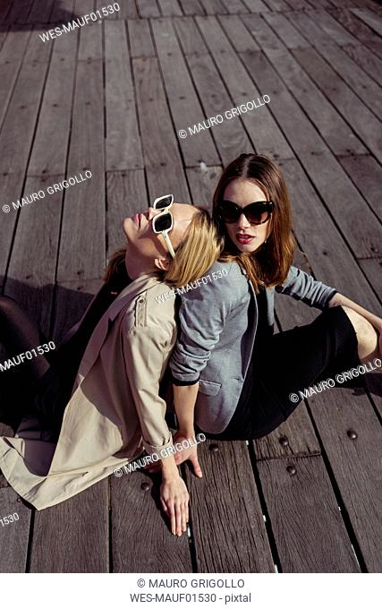 Portrait of two fashionable young women sitting on wooden floor wearing sunglasses