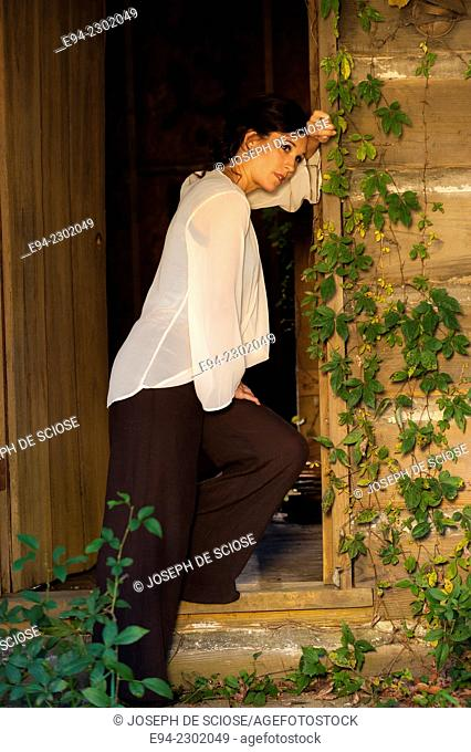 36 year old brunette woman outdoors standing in a doorway of an old house