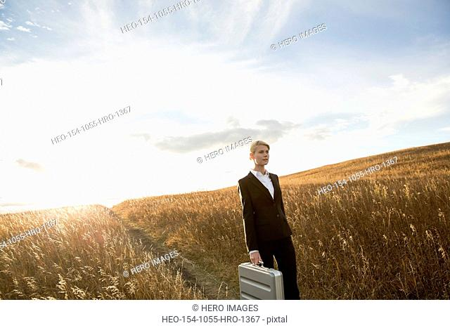 Businesswoman with briefcase standing in field