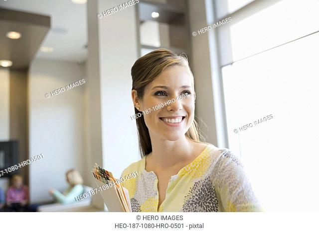 Confident receptionist holding medical records in dentists office