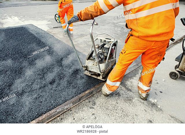Low section of manual worker laying asphalt at construction site