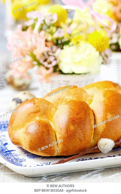 Easter bun and beautiful decorations with spring flowers in the background. Festive dish