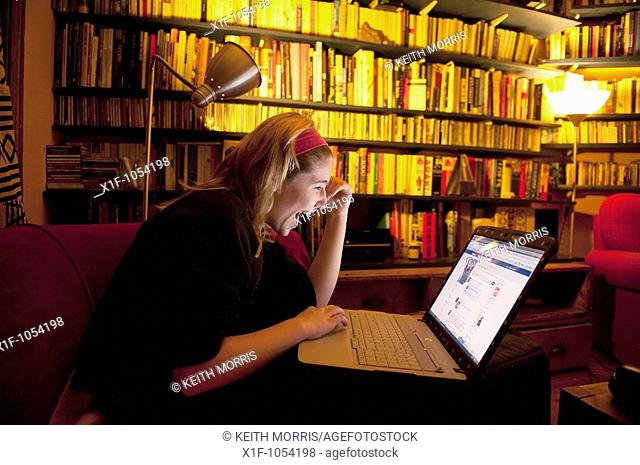 A teenage girl reading her Facebook page on a laptop computer at home, UK