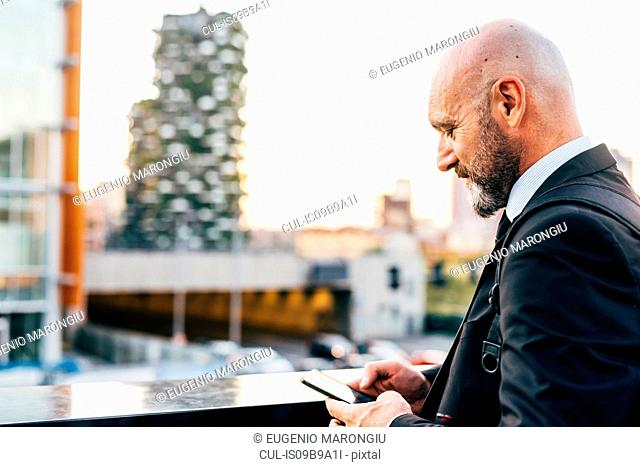 Mature businessman standing outdoors, using smartphone
