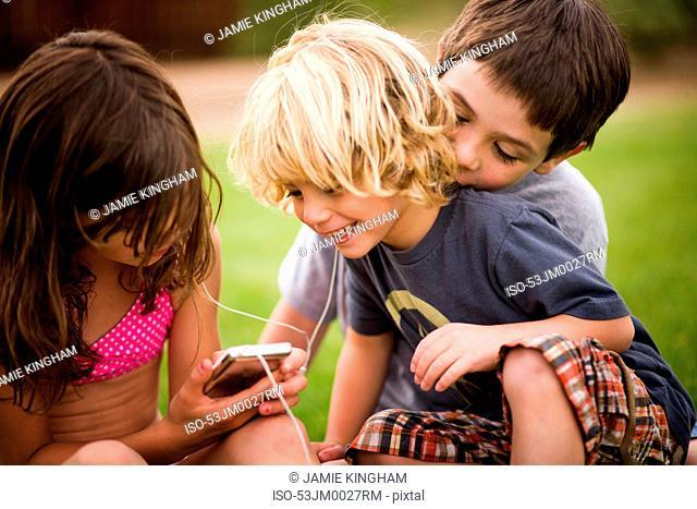 Children listening to earphones outdoors