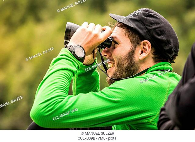 Young male backpacker looking through binoculars in Queulat National Park, Chile