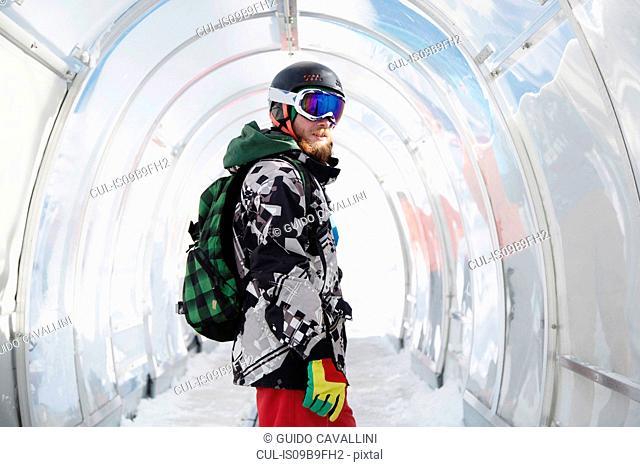 Portrait of snowboarder in ski run tunnel