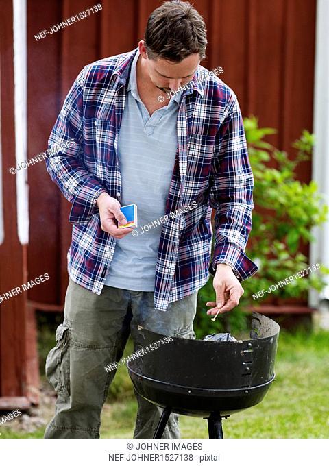 Man preparing grill for barbecue