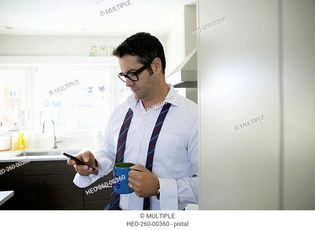 Businessman drinking coffee using cell phone in kitchen