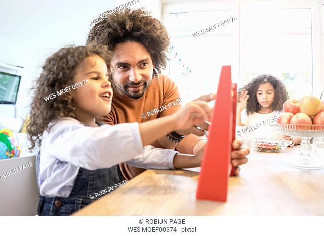 Father sitting at table with his daughter learning to caculate with a slide rule