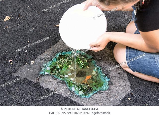 27 July 2018, Germany, Moenchengladbach: The artist Maren Doerwaldt fills synthetic resin into a pothole which is being transformed into a work of art