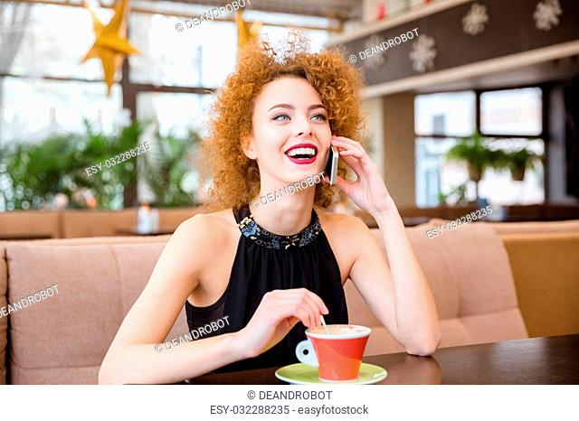 Portrait of a laughing redhead woman talking on the phone in restaurant