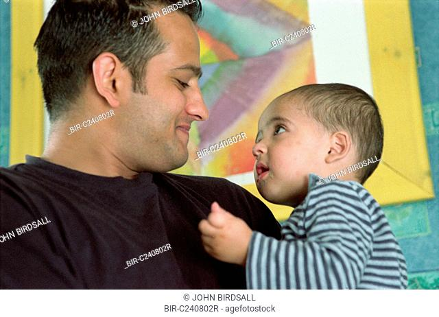 Father holding young son, smiling