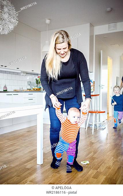 Full length of mother assisting baby in walking whine boy running at home