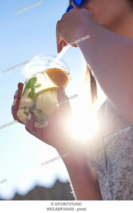 Woman drinking lemonade from plastic cup, close-up