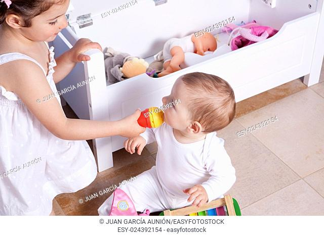 Baby boy playing with his sister at toys room. They are singing with a toy microphone