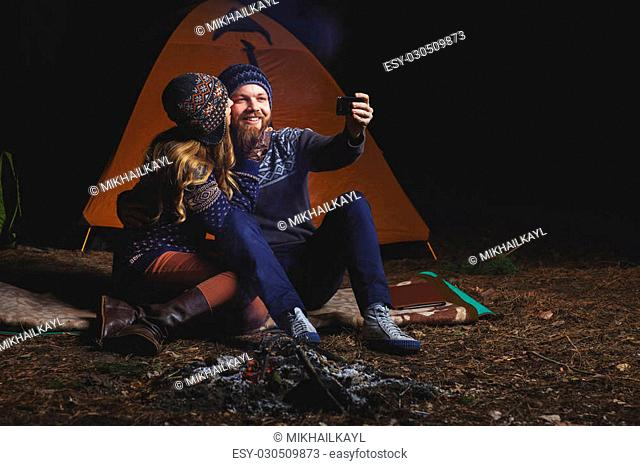 Couple tent camping in the wilderness taking selfie