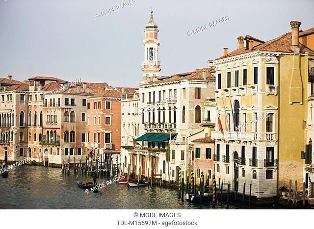 The spire of Bell Tower of Santi Apostoli Church and Grand Canal, Rialto Bridge, Venice, Italy
