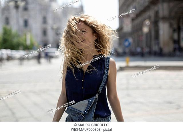 Italy, Milan, smiling young woman tossing her hair