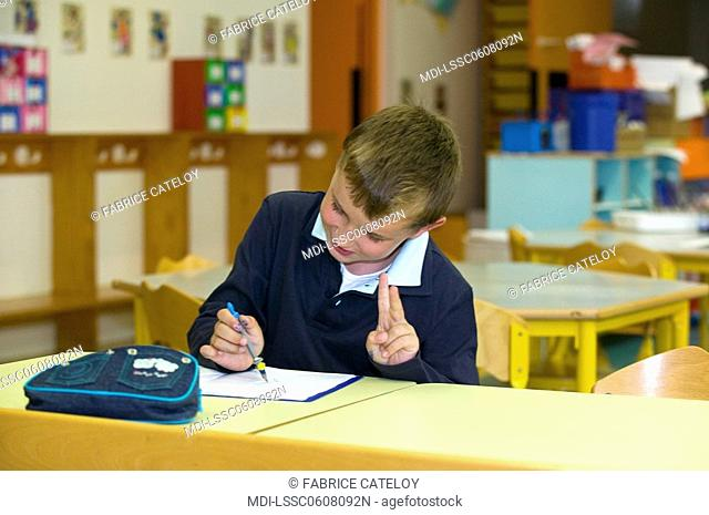 Young boy working in a classroom and showing peace sign