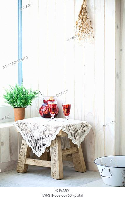 Two glasses full of juice and jug on table near potted plant