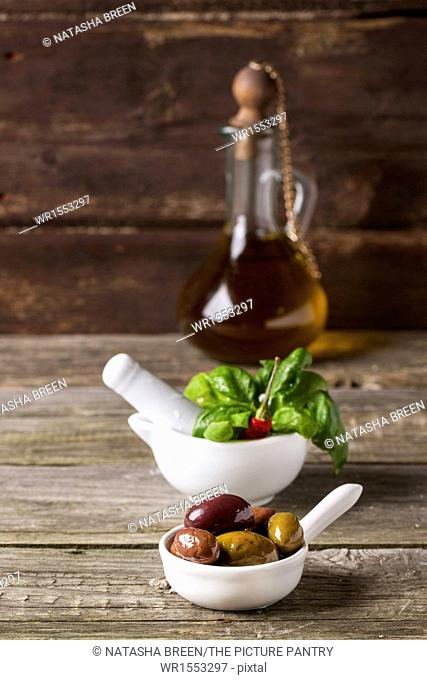 Mix of olives with fresh basil in white mortar and vintage bottle of olive oil on old wooden table