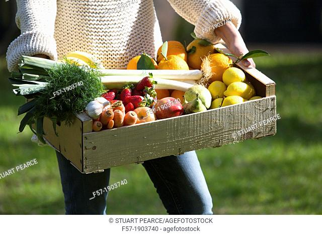 Woman carrying a wooden crate of healthy fruit & vegetables