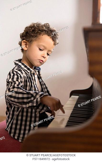 Four year old boy playing the piano