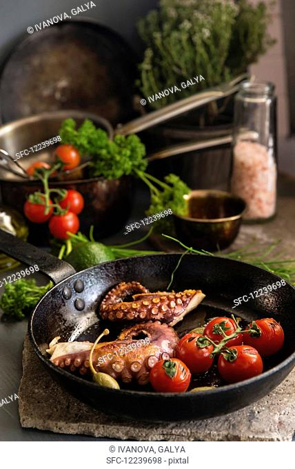 Fried octopus with tomatoes and capers in a pan