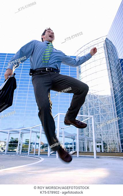 businessman jumping with joy outside modern office building