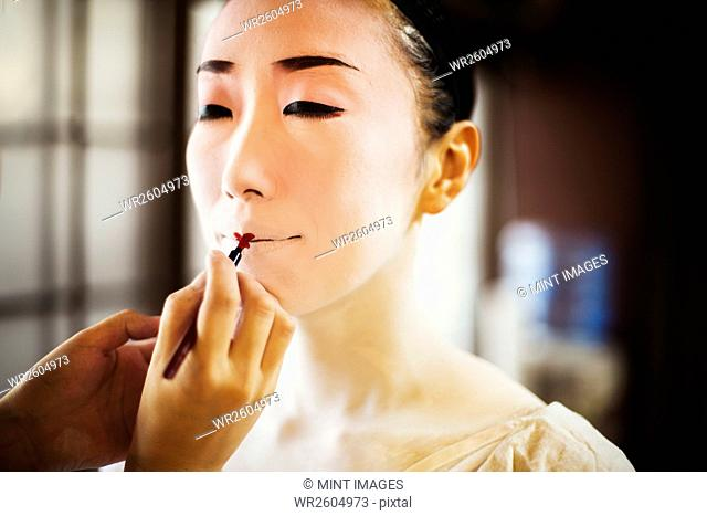 A modern woman creating the traditional geisha vivid red lips by painting on lipstick with a fine brush. White face makeup
