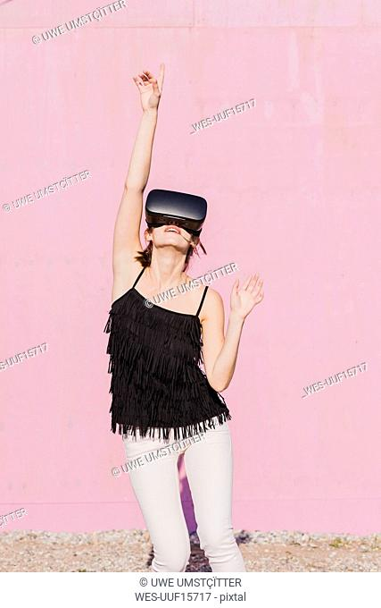 Young woman wearing VR glasses moving in front of pink wall