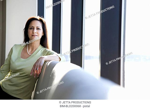Mixed race businesswoman sitting in lobby