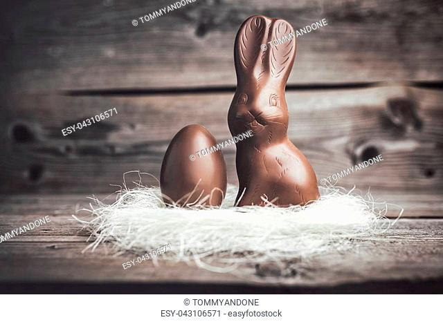 Delicious chocolate Easter bunny and egg on wooden background
