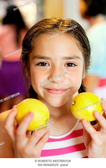 Girl holding two lemons